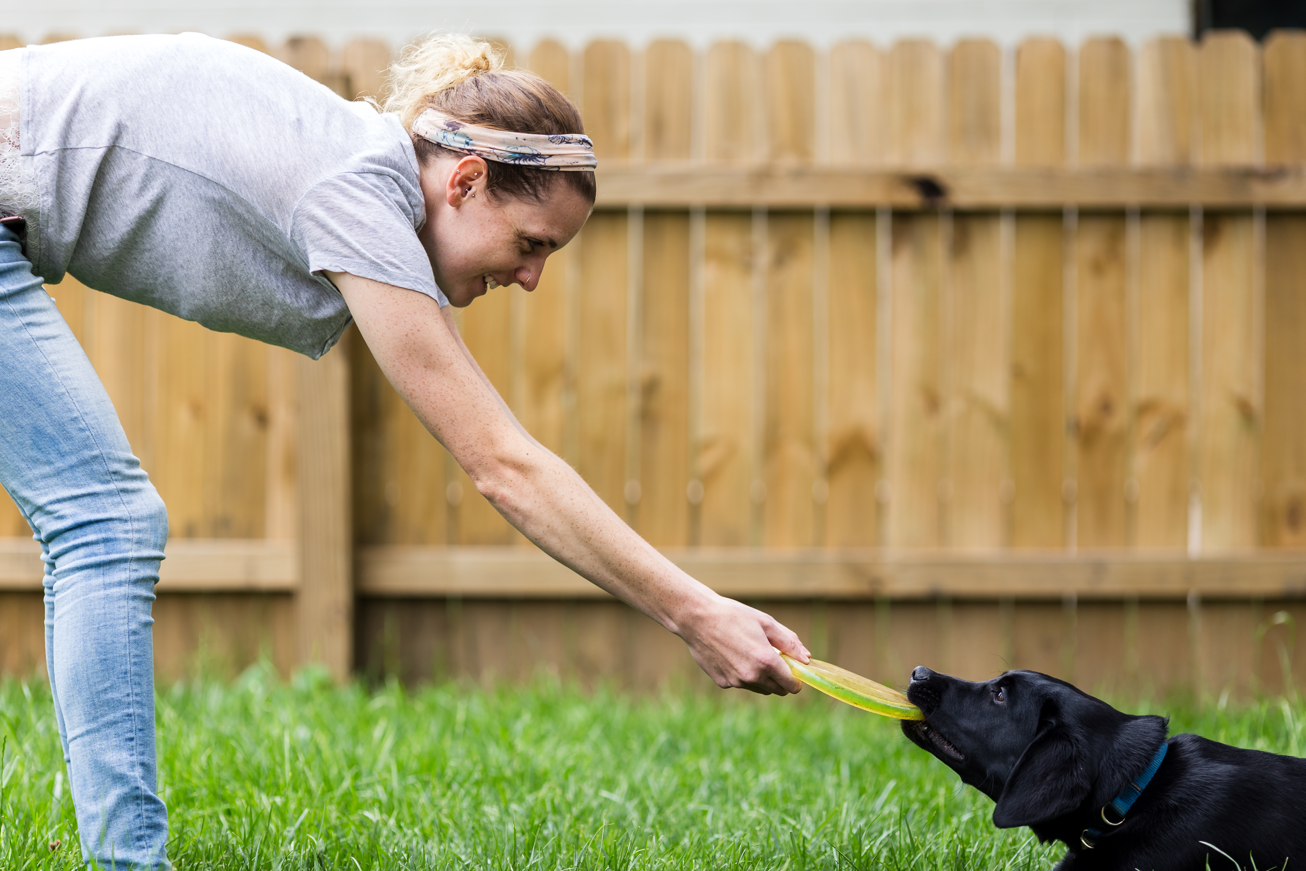 women and black lab dog with Frisbee
